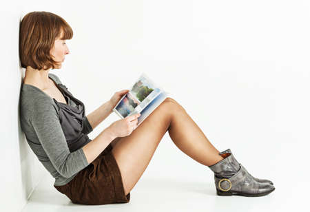siting: Middle aged woman sitting on the floor with a book