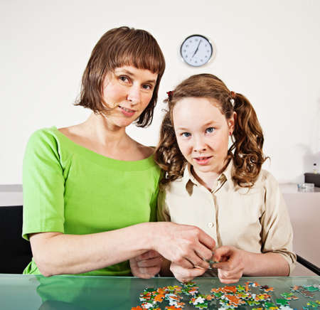 Teenager girl and her mother doing a puzzle at home Stock Photo - 17166000