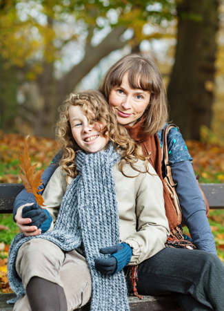 Smiling mother and her teenager daughter sitting on a bench in an autumn park photo