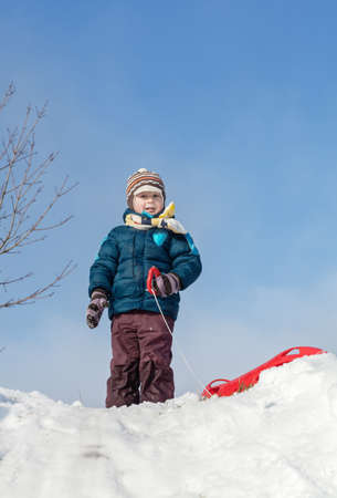 Boy standing with red plastic sleigh on a snowy hill in sunny winter day Stock Photo - 17165997