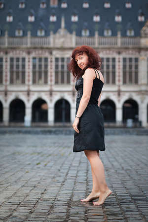 tiptoe: Portrait of mature redhair woman standing in city square