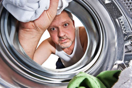Man loading cloths to washing machine. View from inside the washing machine. photo