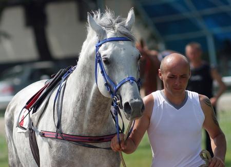 PYATIGORSK, RUSSIA - JULY 17: An unidentified groom and grey arabian horse,stallion Tungus after winning the Pesnyara race on Jule 17, 2011 in Pyatigorsk, Caucasus, Russia.  Stock Photo - 10005889