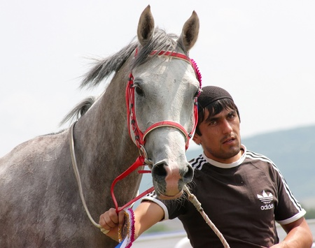 PYATIGORSK, RUSSIA - AUGUST 21: An unidentified groom and arabian horse, grey mare Pirma after race for the prize of Bolshoi Sprinterski on August 21,2011 in Pyatigorsk, Caucasus, Russia.  Stock Photo - 10404544