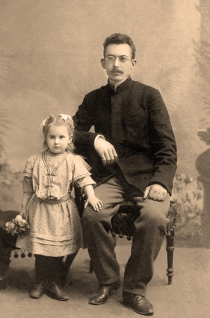 old photo: Portrait of a family from the 1909s. This is a sepia-toned desaturated color file.