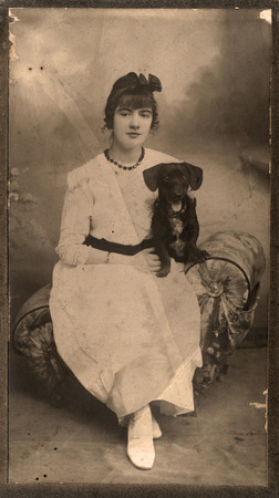 russian ethnicity: Portrait old beautiful girl with a dog,1915 year. Stock Photo
