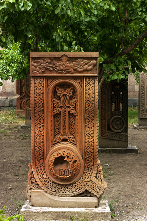 cruz roja: An old carved cross in tufa,Armenia.(Khachkar in the form of letters of the Armenian alphabet).