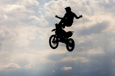 silueta ciclista: Silueta de salto piloto motorcircle en fondo del cielo. Foto de archivo
