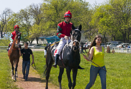 Pyatigorsk,Russia - May 02,2013:Horse racing is a popular sport in Russia and betting is possible.Before the horse race for the Otkritia prize, two horses and jockeys pass the sand track.Racecourse one of the oldest in Russia. Sajtókép