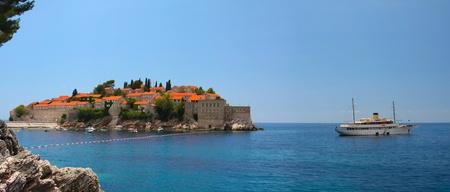sveti: panorama Sveti Stefan on a sunny day and a yacht near the island