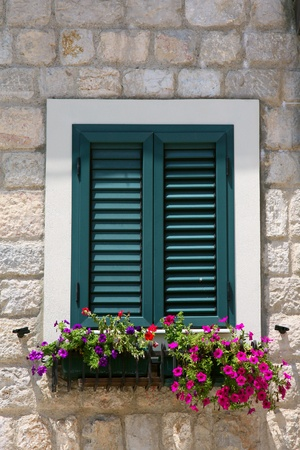 wooden shutters on the windows in traditional style with flowers Stock Photo
