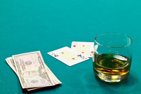 a glass of liquor and cards and dollars photo