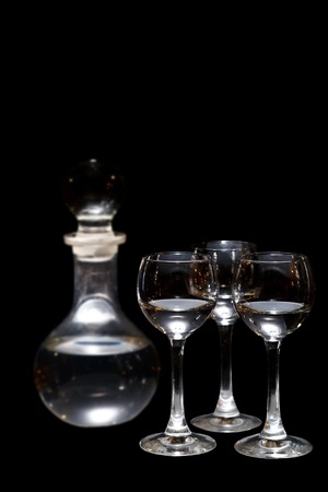 three glasses of vodka and a bottle isolated photo