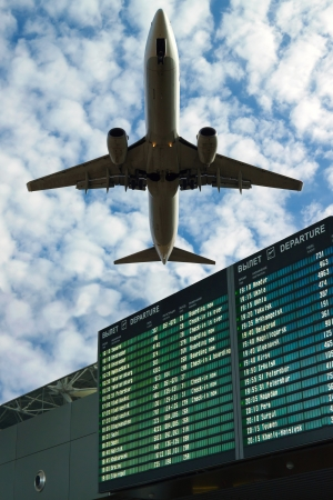 Airport flight information with the list of flights in the sky and the plane Stock Photo