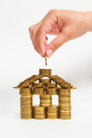 Front view of a house built coins female hand on a light background