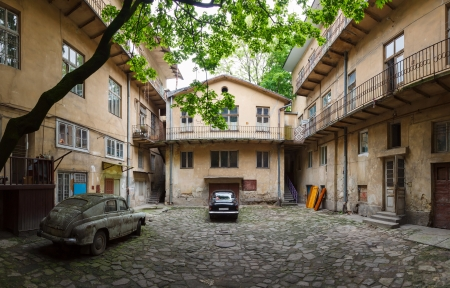 black vintage car and old rusty car in the old courtyard of the city Lviv photo