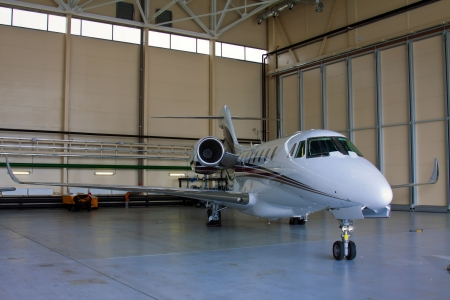 corporate jet: Silver private jet with two engines in the hangar