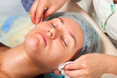 cosmetologist: cosmetologist doing facial massage with a young woman applying cream