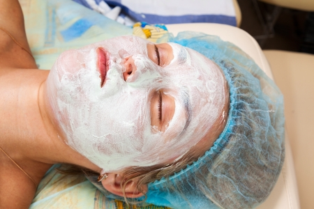 application of a cosmetic mask on the face of young woman at the beautician photo
