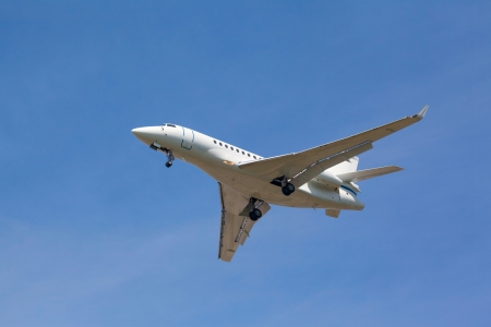 view from below on the white jet passenger aircraft with the gear against the blue sky photo