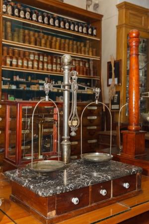 balanza de laboratorio: viejas balanzas médicas contra el gabinete con los medicamentos en la farmacia