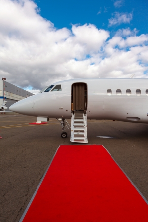 corporate jet: ladder in a private jet and red carpet on blue sky Stock Photo