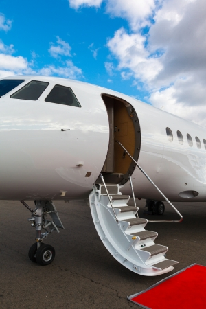 ladder in a private jet and red carpet on blue sky photo