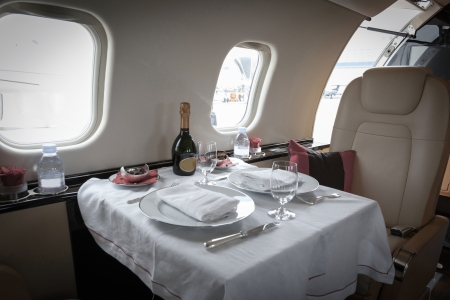 corporate jet: Luxury interior aircraft business aviation decorated table Stock Photo
