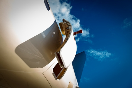 private parts: open door and tail in private jet against the blue sky