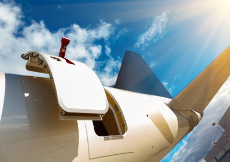 private cloud: open door and tail in private jet against the blue sky
