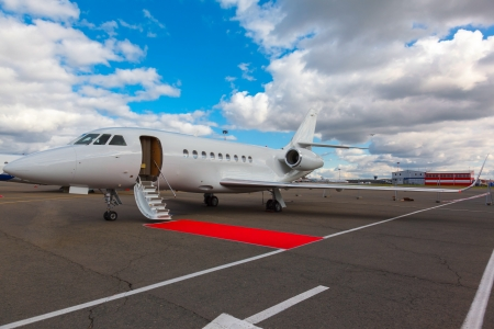 corporate jet: White reactive private jet, the front landing gear and a ladder on blue sky and clouds