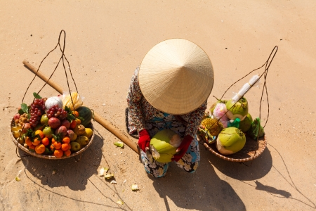 'vietnamese: Vietnamese woman in a straw hat on the beach selling fruit and reveals the coconut