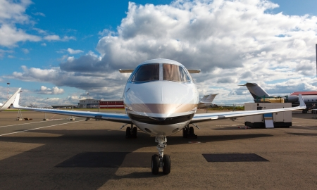 private jet: White reactive private jet, the front landing gear on blue sky and clouds