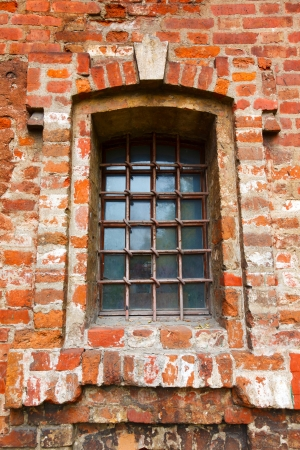 Old window with bars in a red brick photo