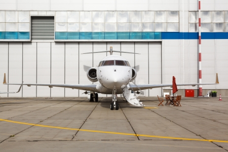 private parts: White reactive private jet, the front landing gear and a ladder Stock Photo