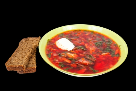 rye bread and a plate with fresh hot borsch isolated on a black background photo