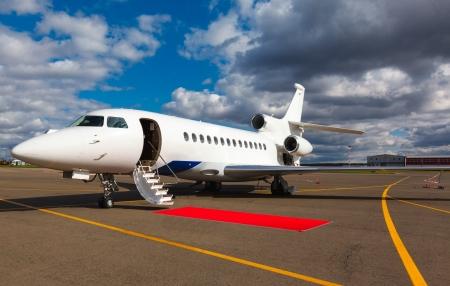Witte reactieve prive-jet, de voorste landingsgestel en een ladder op de blauwe lucht en de wolken
