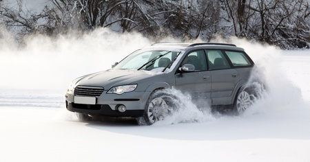 creates: extreme driving, the car is moving rapidly over the smooth snow and creates a spray of snow