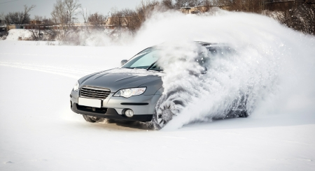 rapidly: extreme driving, the car is moving rapidly over the smooth snow and creates a spray of snow