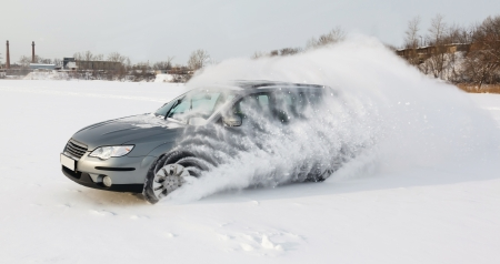 extremes: extreme driving, the car is moving rapidly over the smooth snow and creates a spray of snow