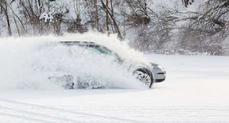 winter storm: extreme driving, the car is moving rapidly over the smooth snow and creates a spray of snow