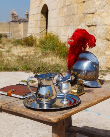 slasher: silver jug with a cup and a medieval helmet with a red pen on the wooden table Stock Photo