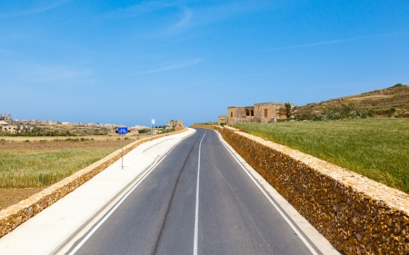 Mediterranean landscape. road, rail fence and a field on a clear day photo