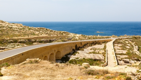 Road and Bridge Azure Window, famous stone arch of Gozo island in the sun in summer, Malta photo