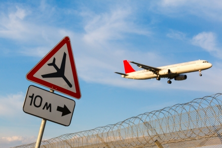 road sign Caution low-flying aircraft on a background of blue sky and aircraft with the gear photo