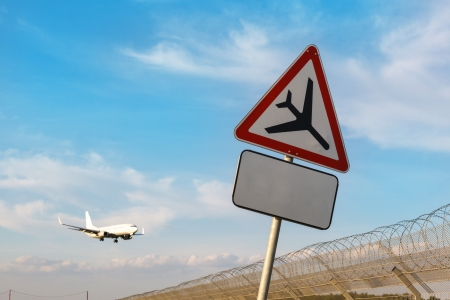 road sign 'Caution low-flying aircraft' on a background of blue sky and aircraft with the gear photo