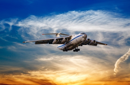 cargo aircraft is landing on the background of sunset