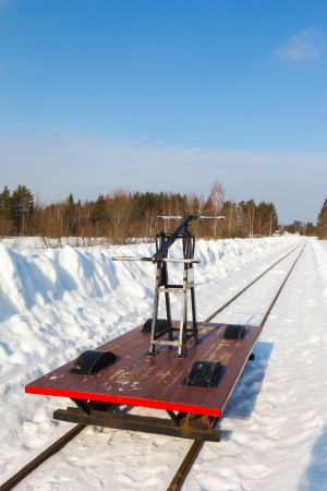 handcar on a narrow track in snow and blue sky photo