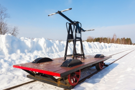 forest railroad: handcar on a narrow track in snow and blue sky Stock Photo