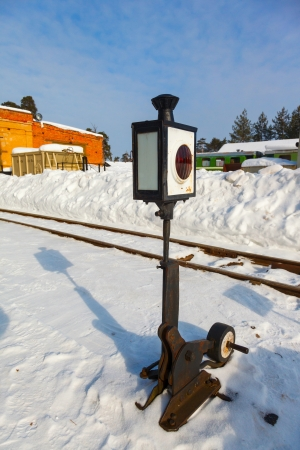 forest railroad: old railway arrow with a lantern in snow